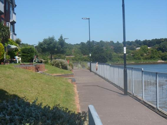 A paved path by the water with railings